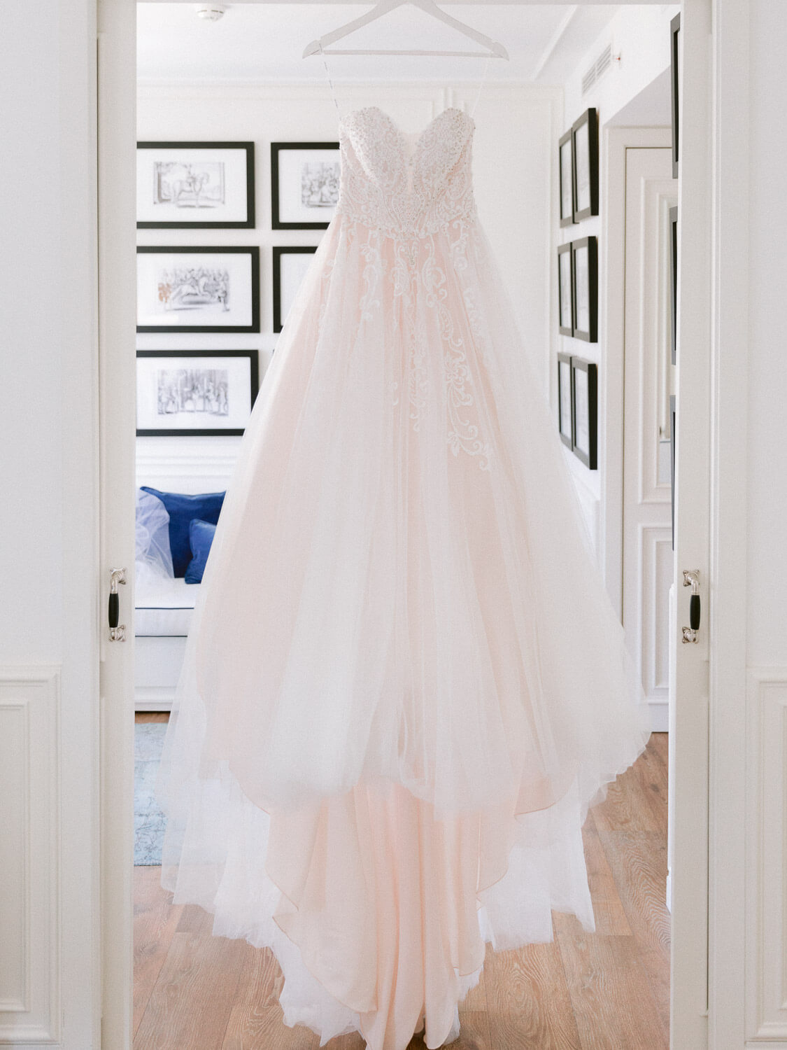 bridal gown with peach hues hanging on door