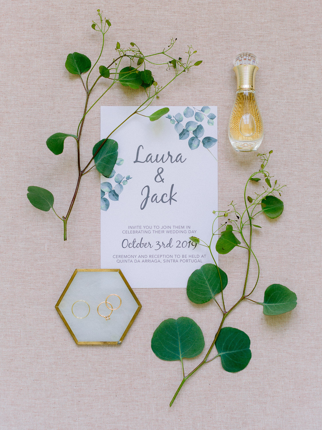 wedding flat lay with wedding bands, perfume, invitation and greenery by Portugal Wedding Photographer