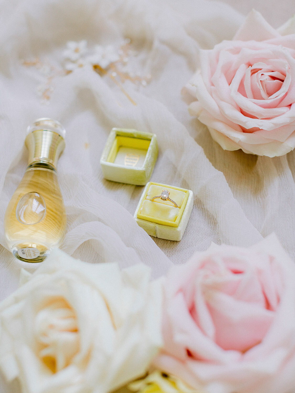 wedding flat with a rose, diamond ring on yellow velvet ring box, perfume and silk by Portugal Wedding Photographer