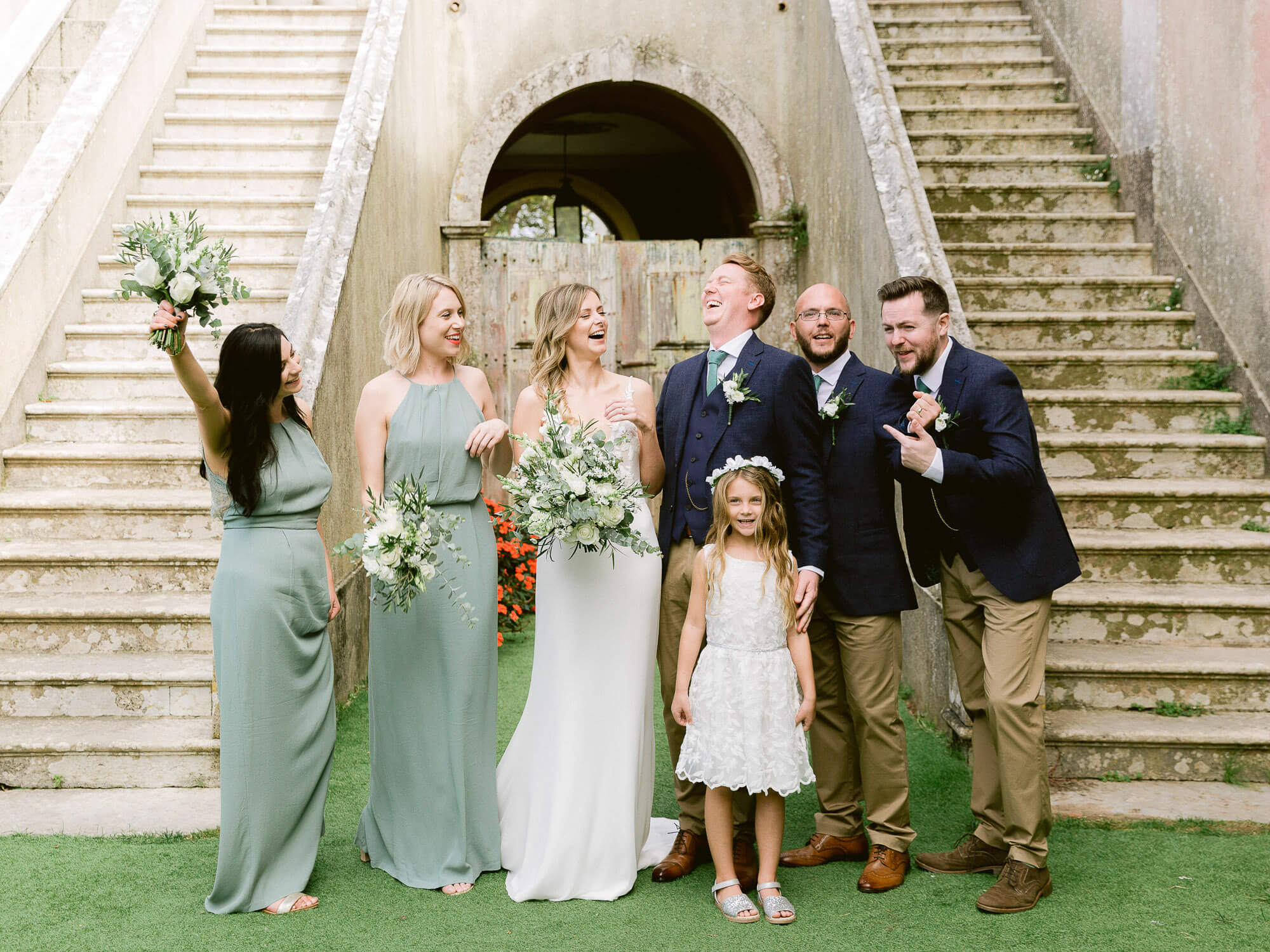 cheering couple, bridesmaids, flower girl, best men portrait after a wedding ceremony by Portugal Wedding Photographer