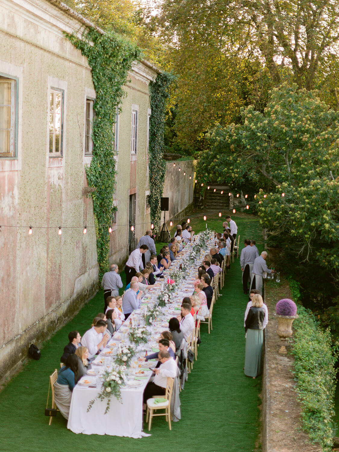 outdoor wedding reception dinner with a long table by Portugal Wedding Photographer
