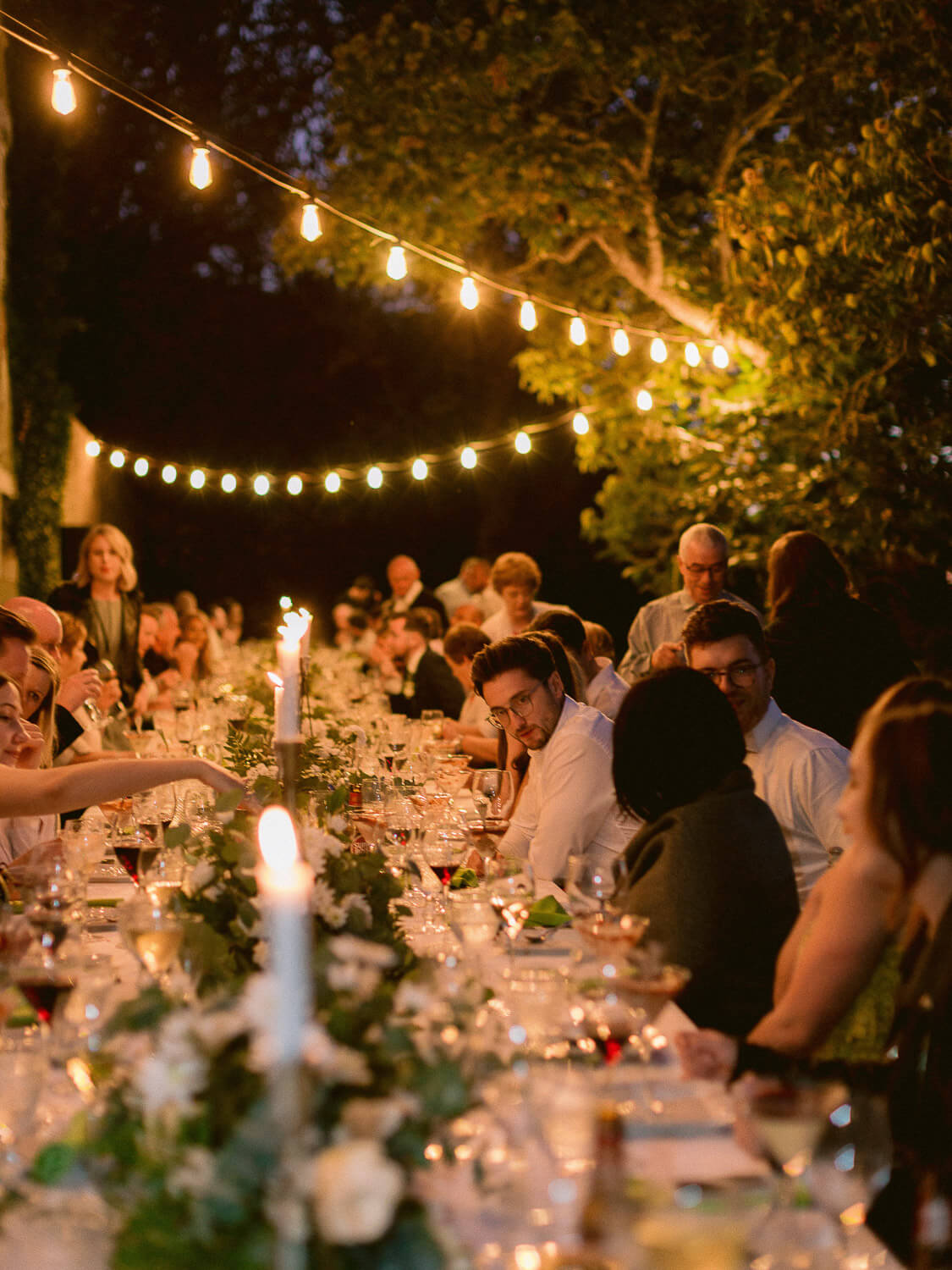 night view of long outdoor reception table and festival lights by Portugal Wedding Photographer
