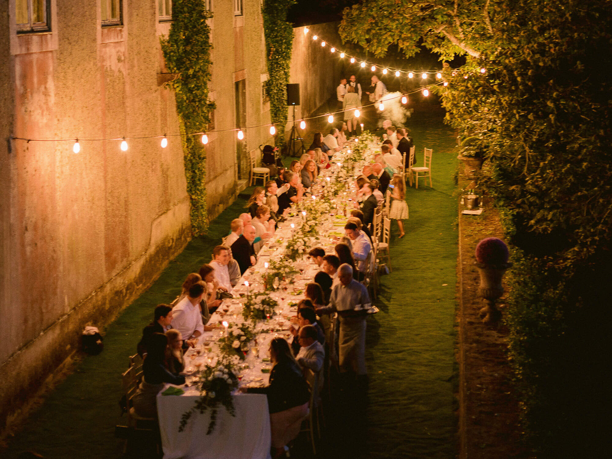 night overview of long outdoor reception table and festival lights by Portugal Wedding Photographer