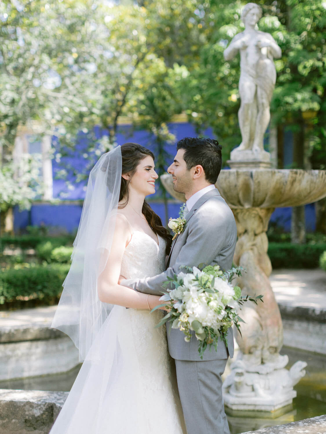 bride and groom enchanted moment by the fountain by Portugal Wedding Photographer