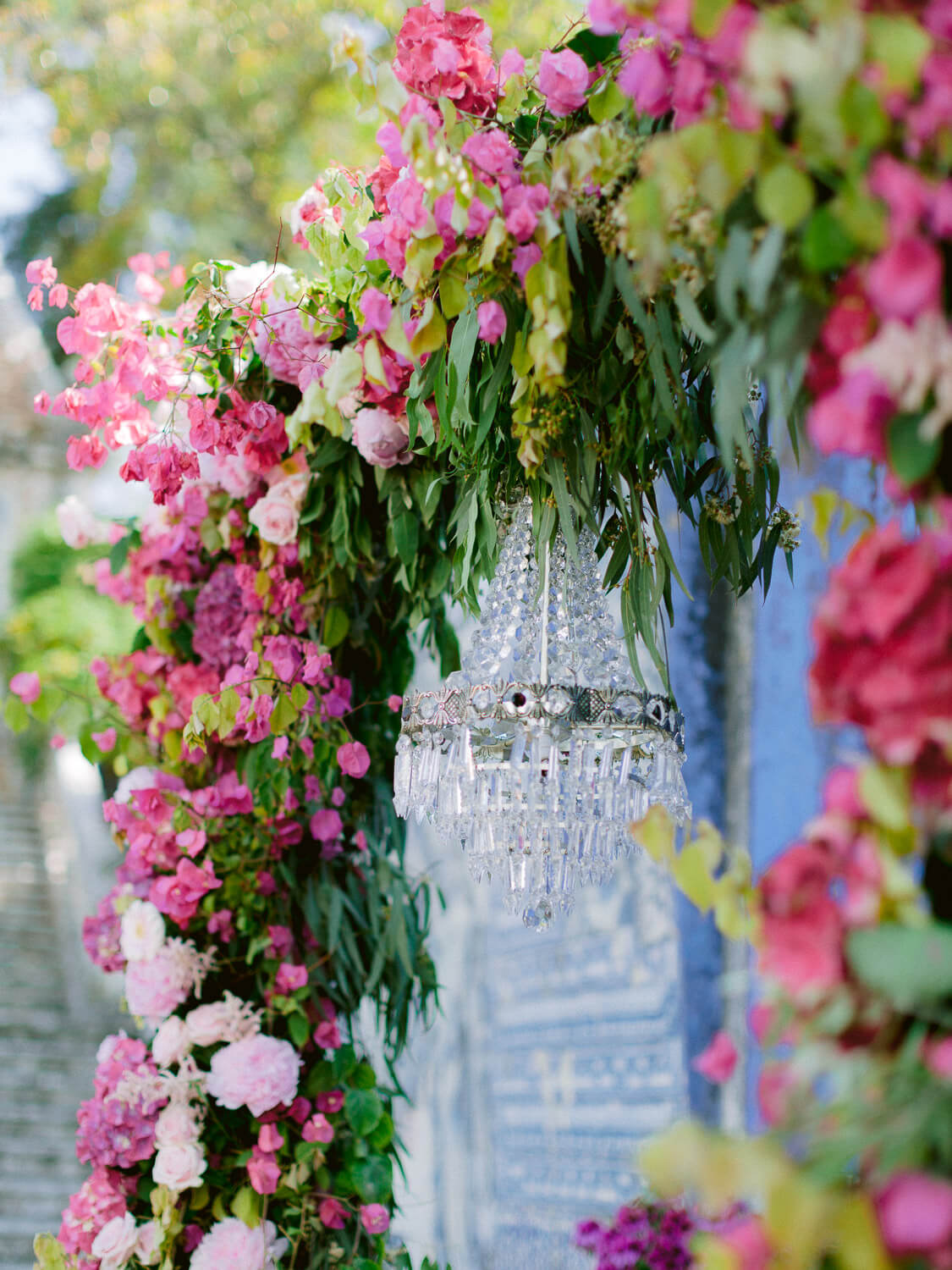 lavish bright pink wedding ceremony floral arch with crystal chandelier by Portugal Wedding Photographer