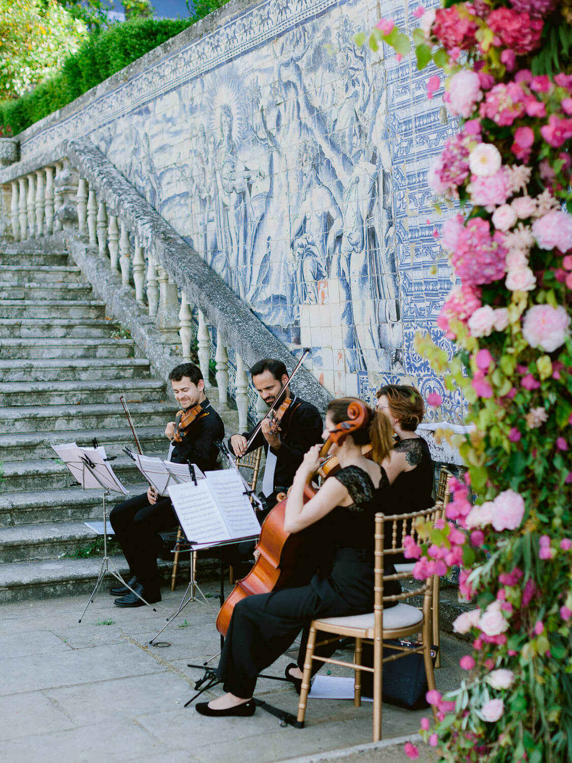 string quartet, wedding floral arch and Portuguese tile wall by Portugal Wedding Photographer