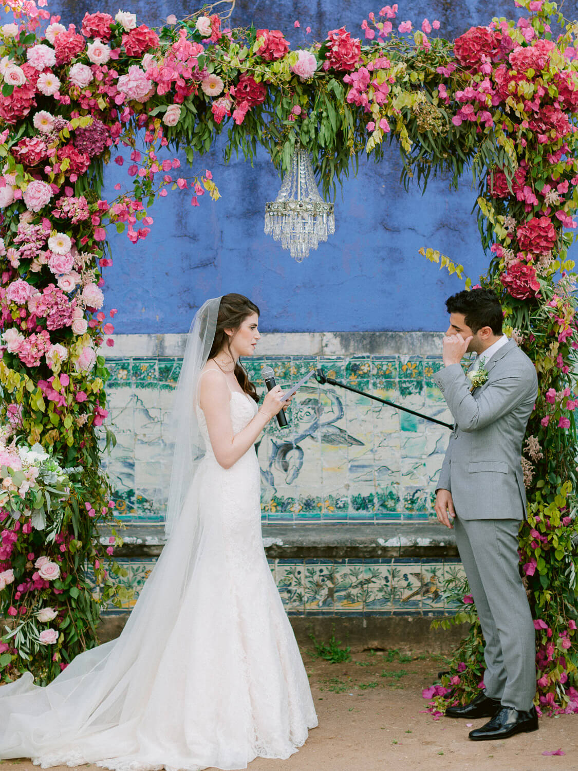 wedding ceremony vow's exchange under bright pink floral arch with crystal chandelier