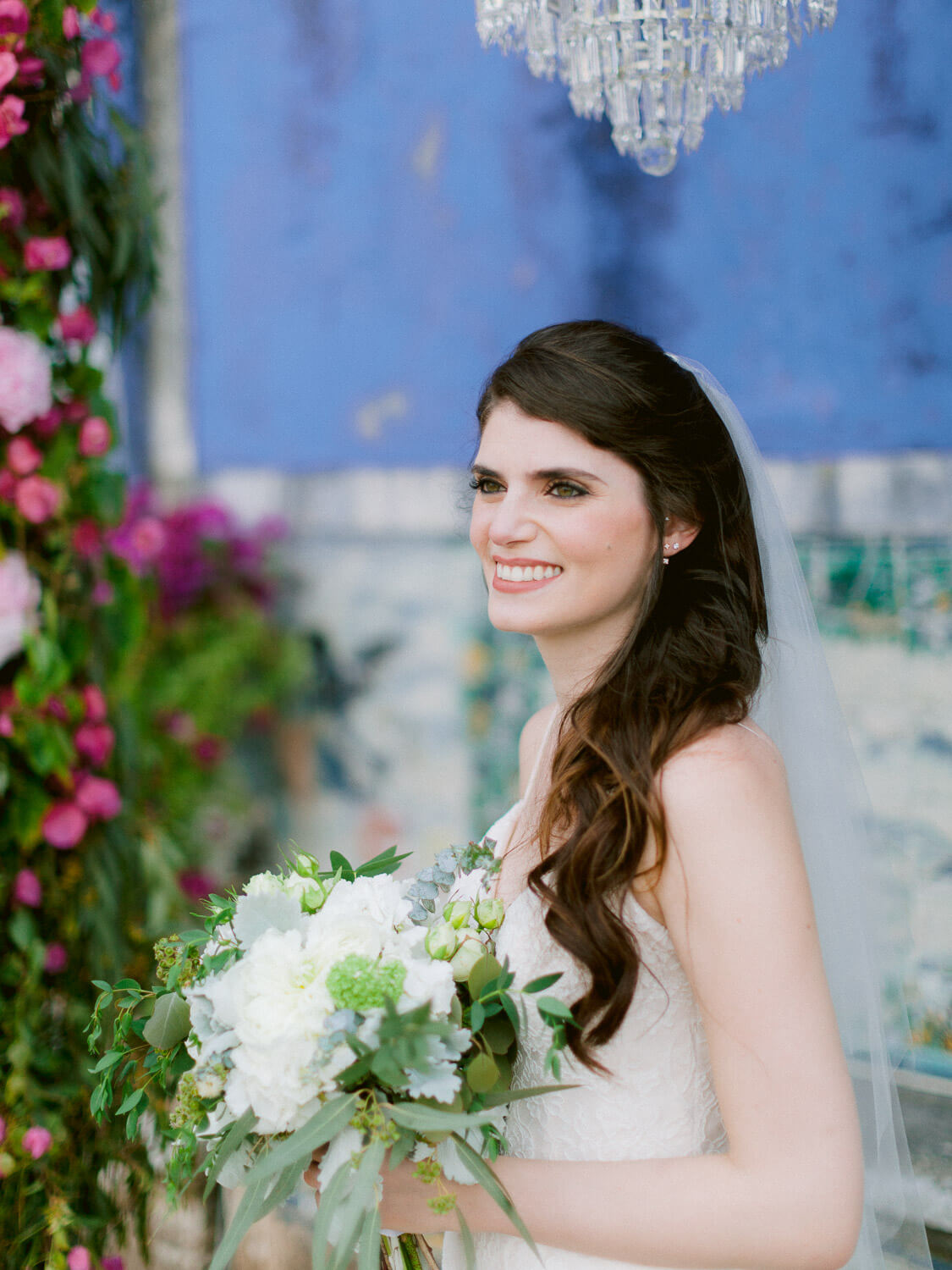 beautiful bride portrait with bright pink floral and blue wall background by Portugal Wedding Photographer