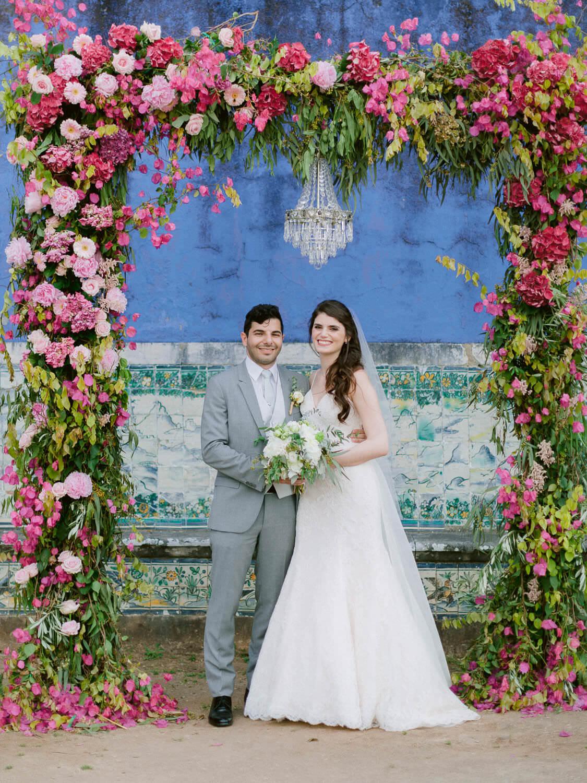 newlyweds under lavish bright pink wedding ceremony arch with crystal chandelier