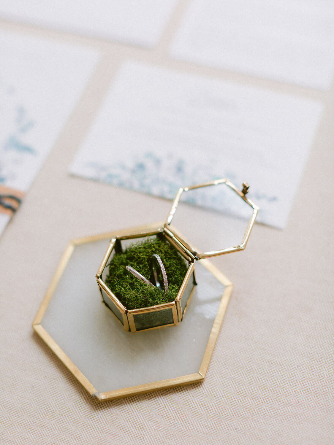 wedding bands in a glass and brass box with moss by Portugal Wedding Photographer