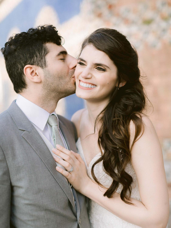 groom sweetly kissing bride on cheek by Portugal Wedding Photographer