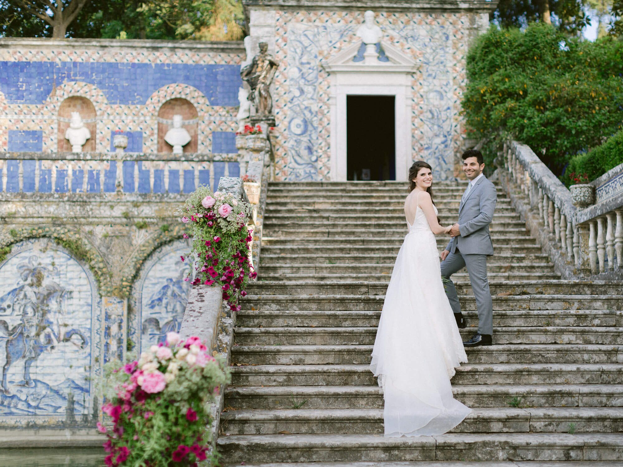happy newlyweds on a staircase and background of Portuguese tiles wall by Portugal Wedding Photographer