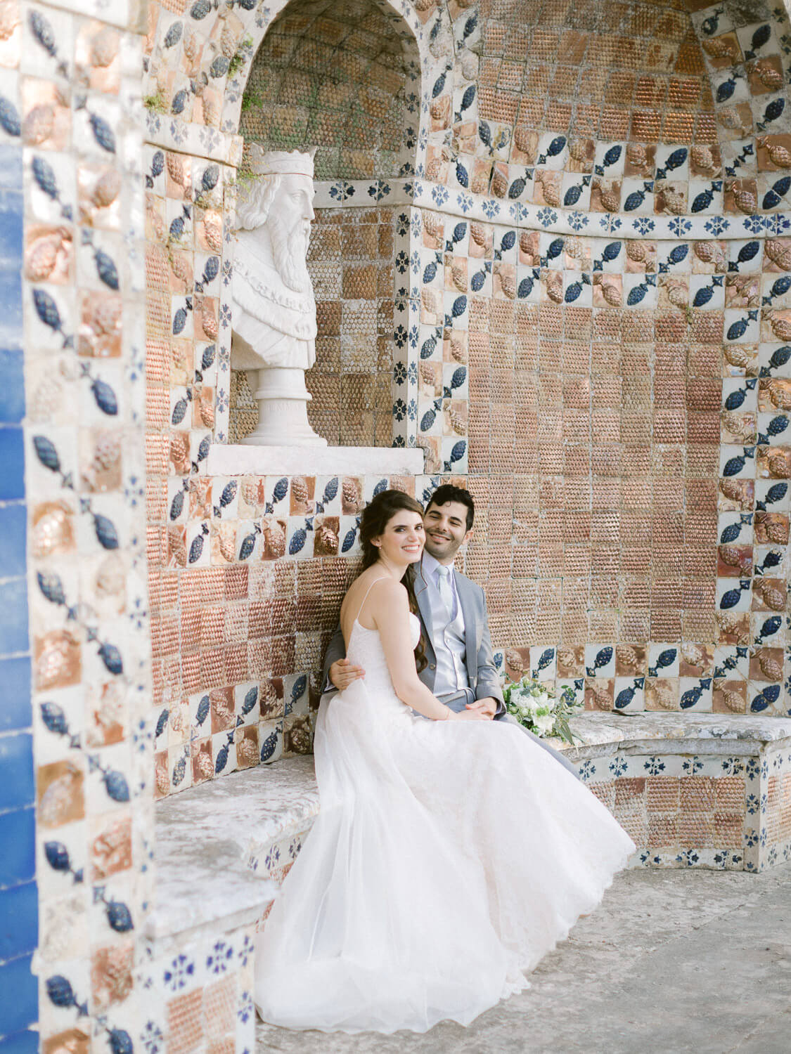 happy wedding couple in a singular corner in Marques de Fronteira Palace by Portugal Wedding Photographer