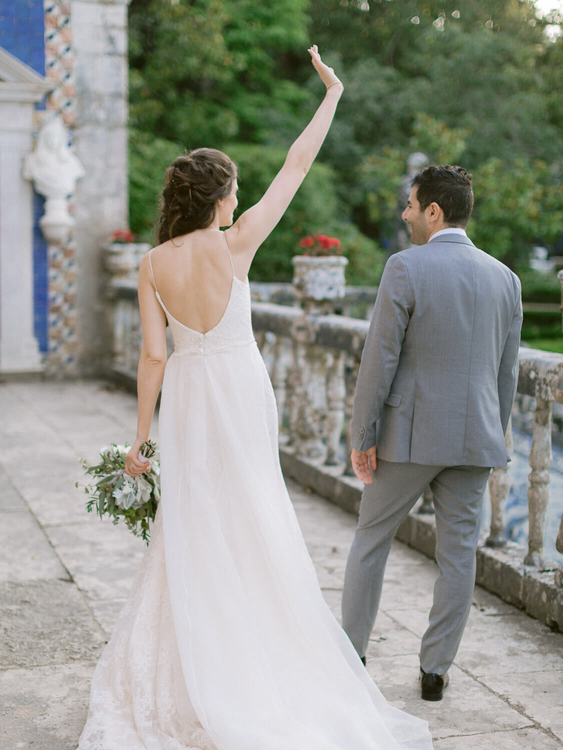 wedding couple portrait with bride waving high to guests by Portugal Wedding Photographer