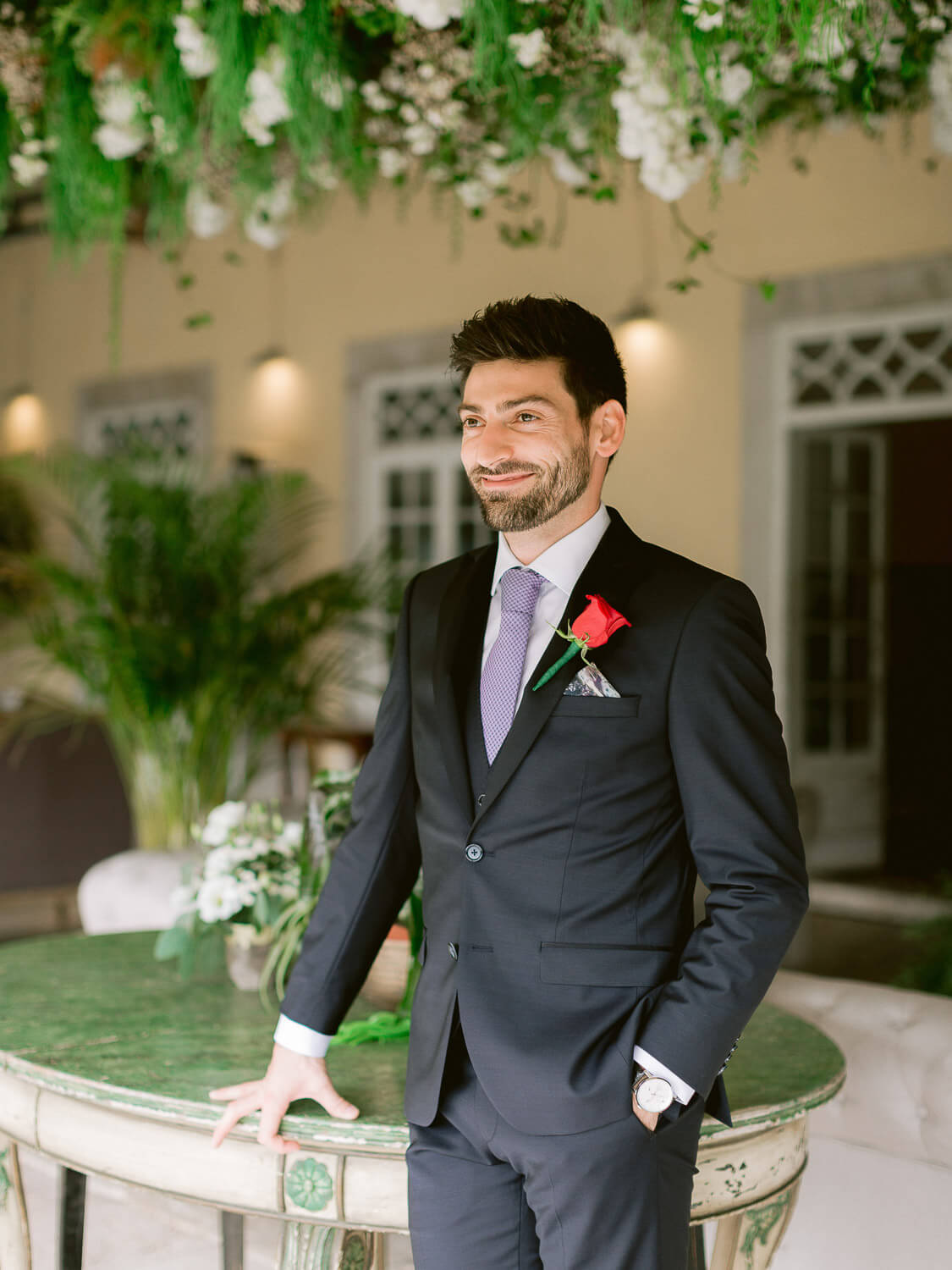 smiling, elegant groom with red boutonnière by Portugal Wedding Photographer