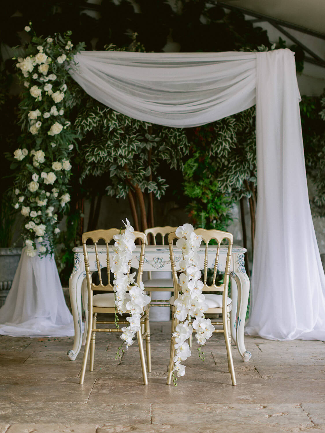 wedding ceremony asymmetric arch and chairs with hanging orchids by Portugal Wedding Photographer