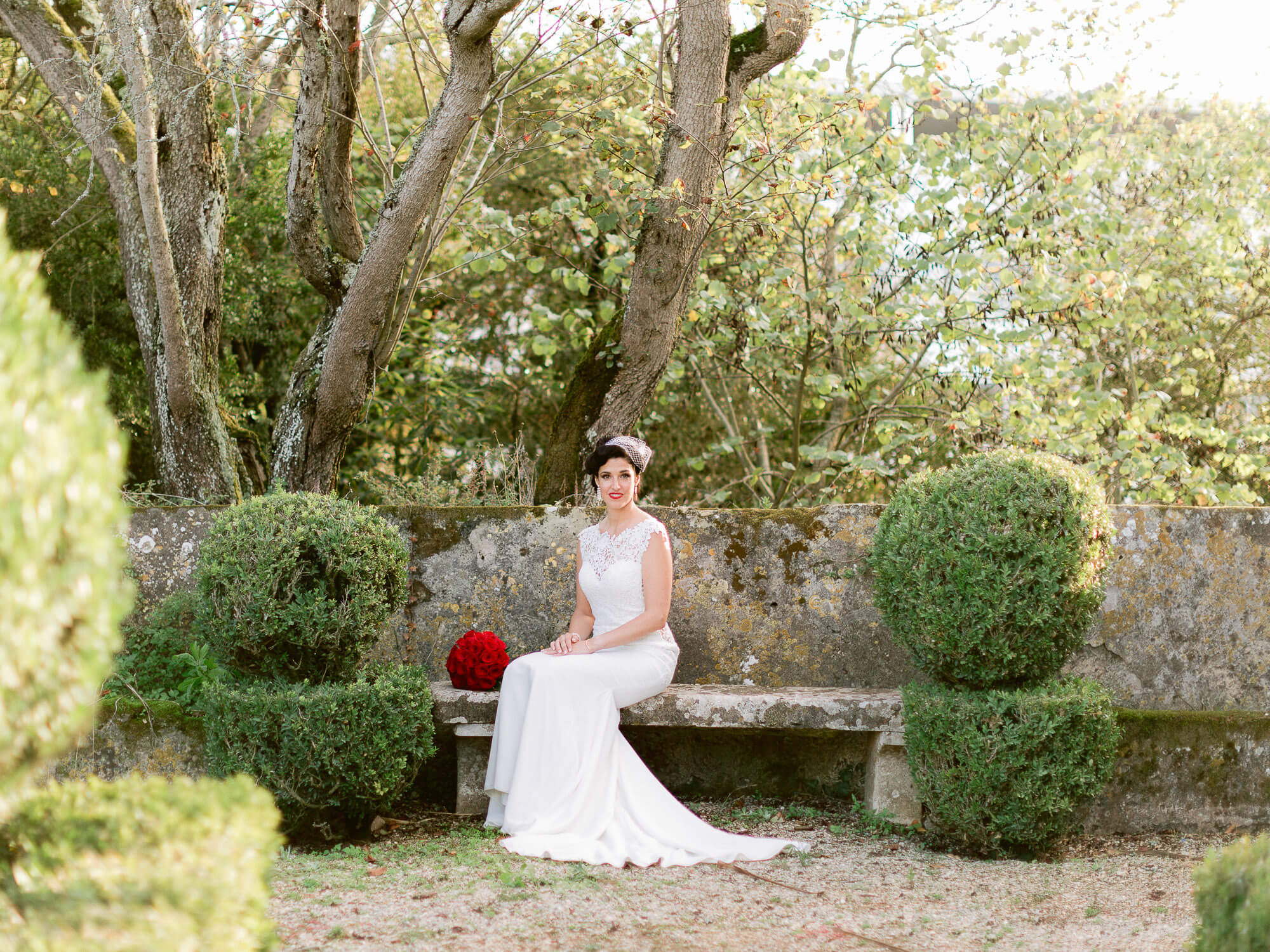 bride sitting down on a french garden with a red bouquet by Portugal Wedding Photographer