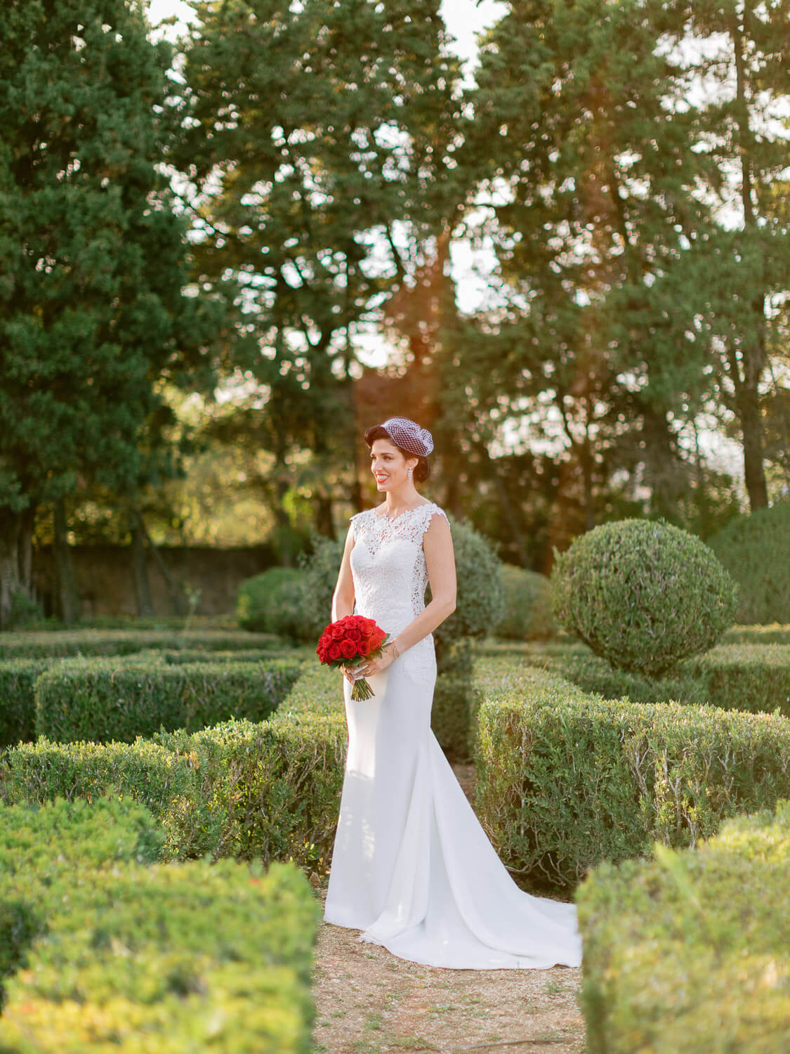 bride beautiful portrait in a french garden with a red bouquet by Portugal Wedding Photographer