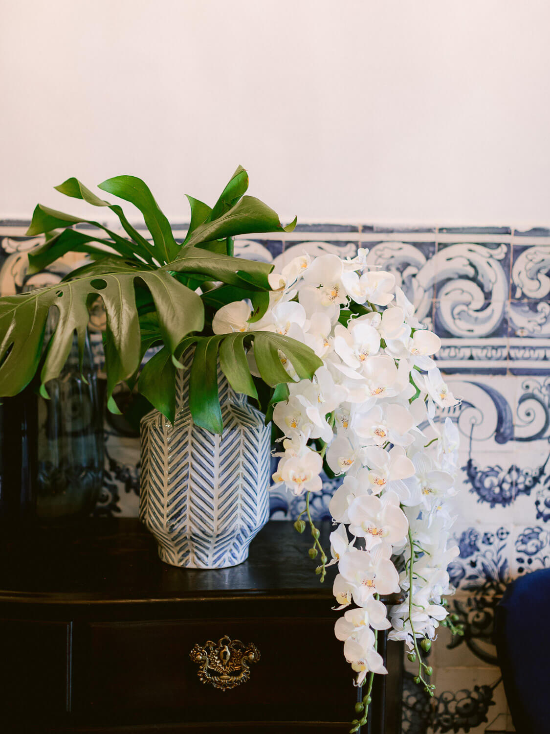 monstera and cascading white orchids with Portuguese wall tiles background by Portugal Wedding Photographer