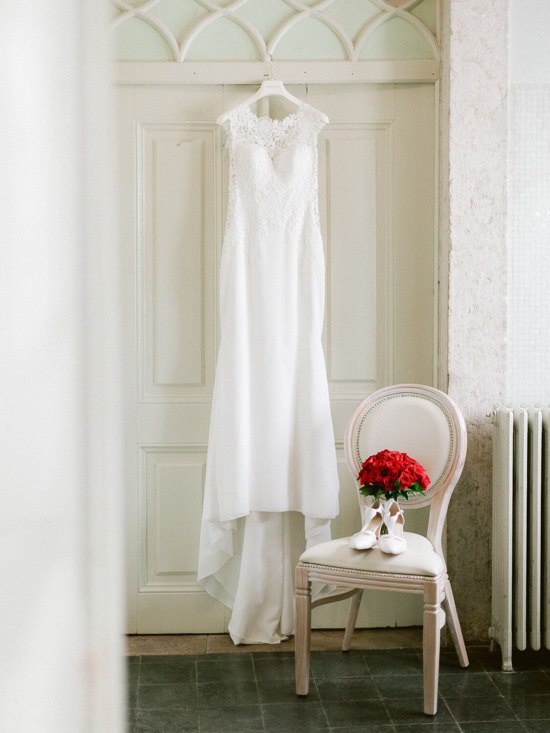 hanging wedding dress, chair with bridal sandals and red roses bouquet by Portugal Wedding Photographer