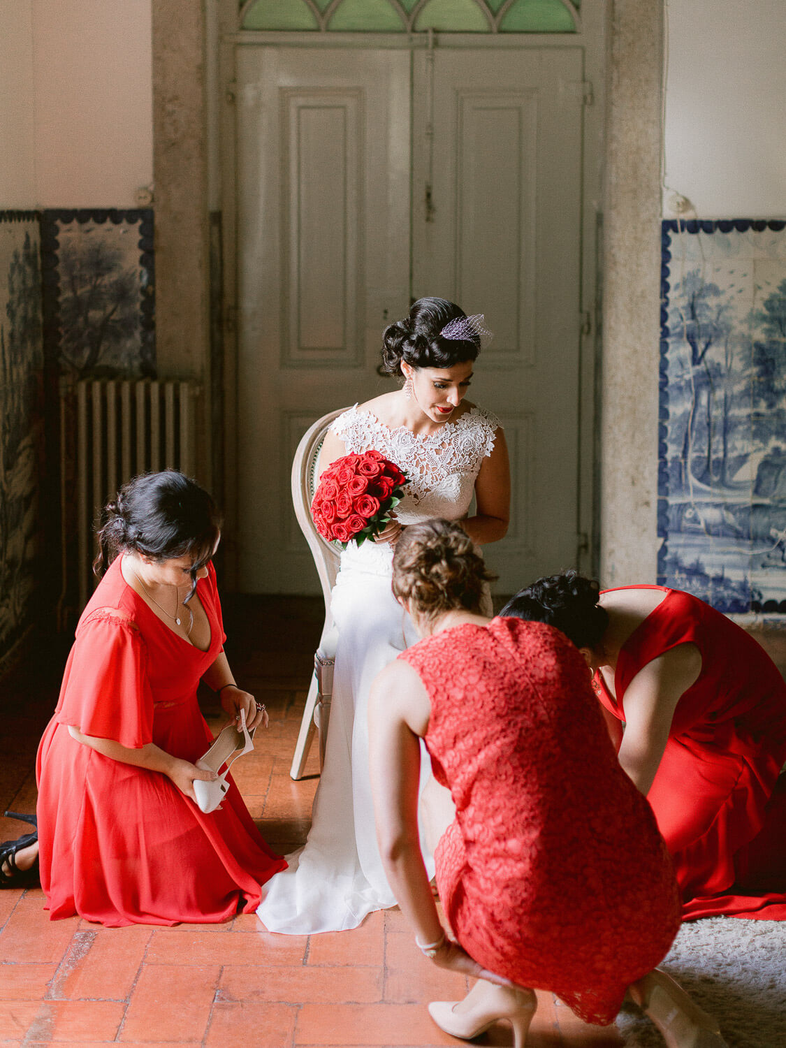 bride and bridesmaids dressed in red with Portuguese wall tile background by Portugal Wedding Photographer