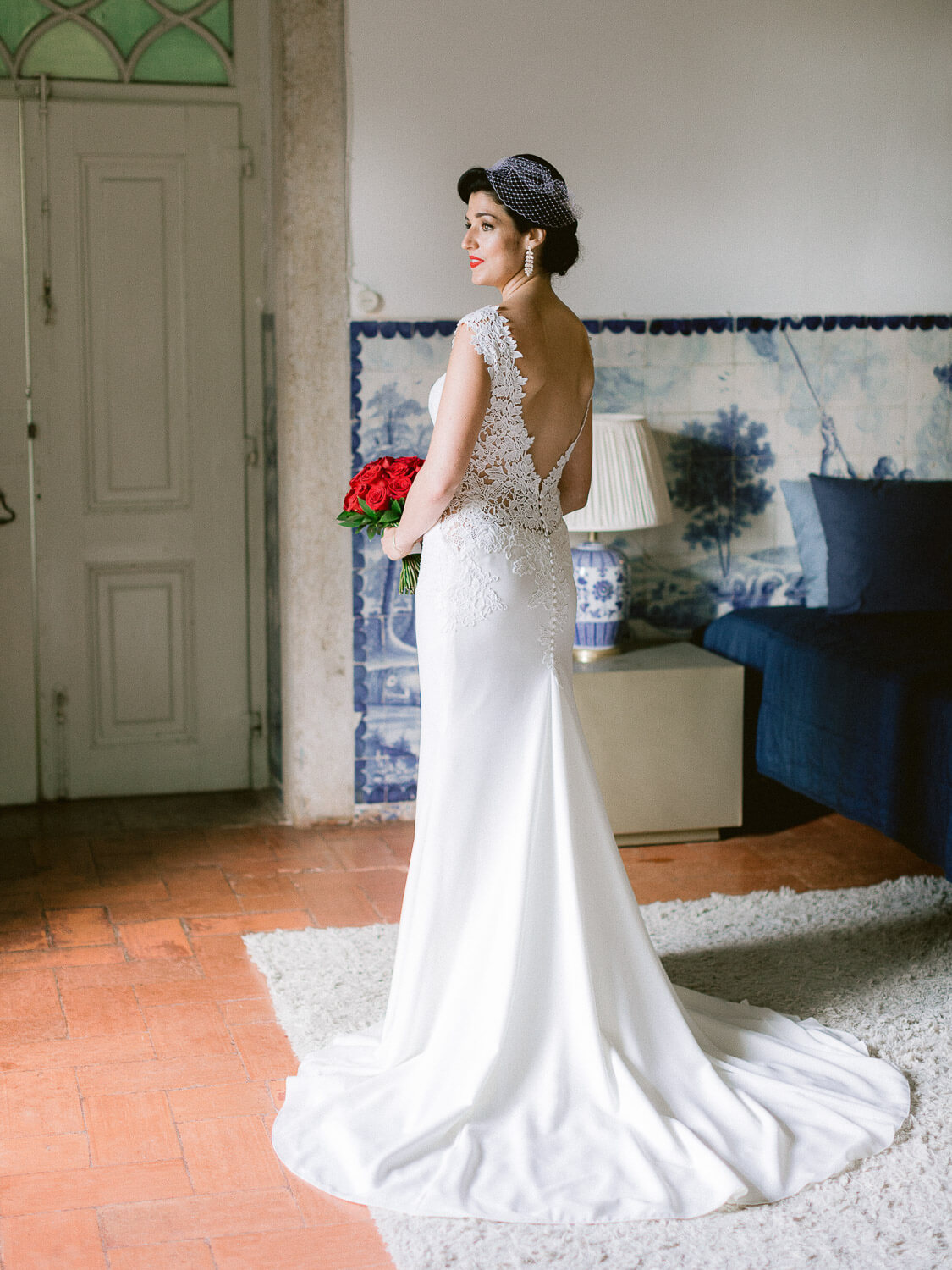 Bride with embroidered plunging back wedding dress and red roses bouquet by Portugal Wedding Photographer