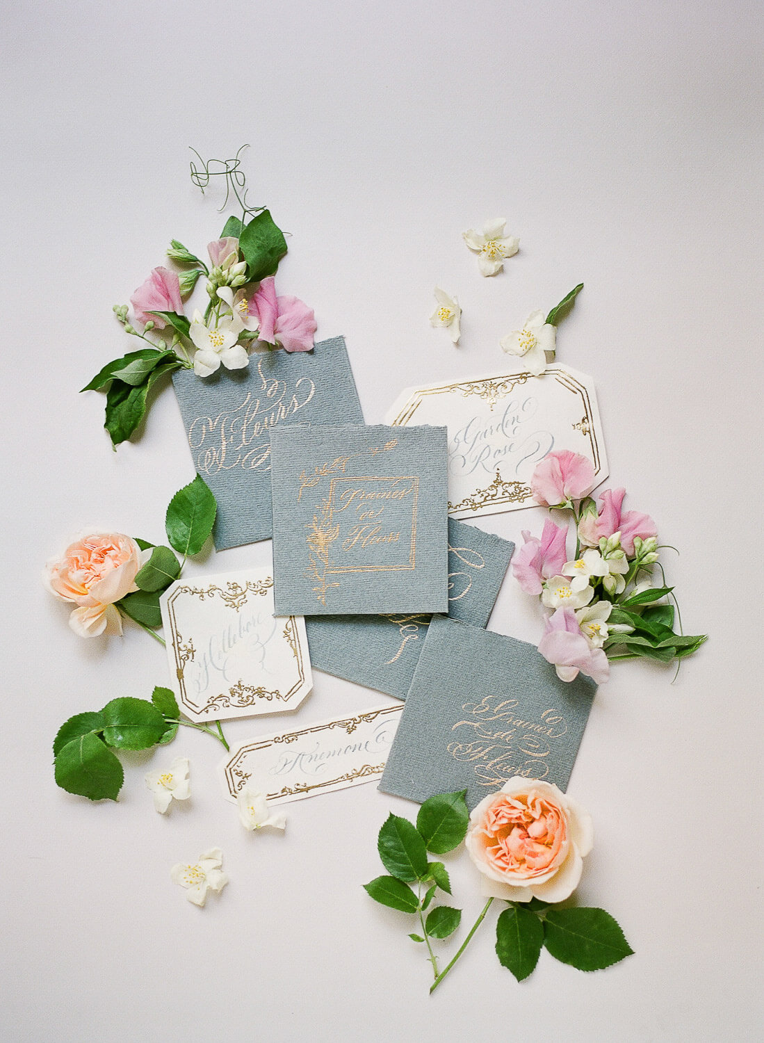 wedding flat lay with calligraphy invitations and floral details by Portugal Wedding Photographer