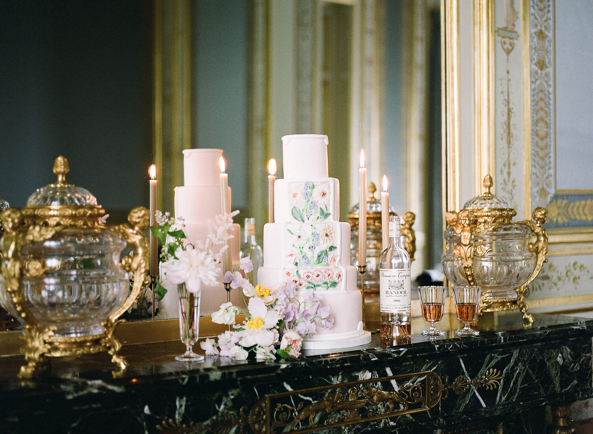 five-tiered wedding cake with pastel florals on mantlepiece by Portugal Wedding Photographer