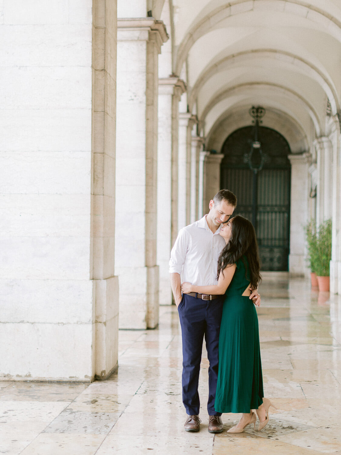 couple kissing in Terreiro do Paço during engagement session by Portugal Wedding Photographer