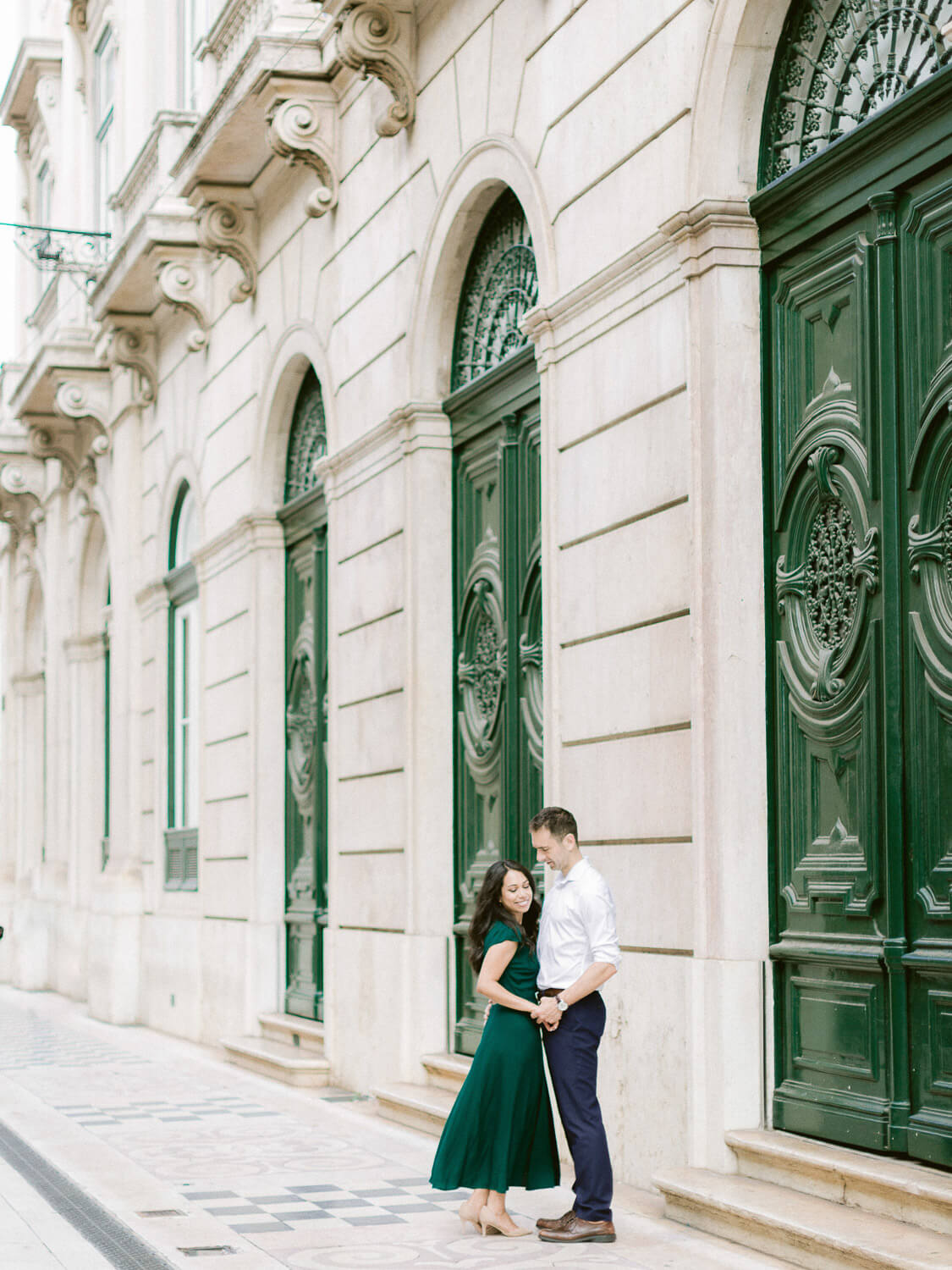 Joyful couple during engagement in Lisbon with typical Portuguese architecture facade by Portugal Wedding Photographer