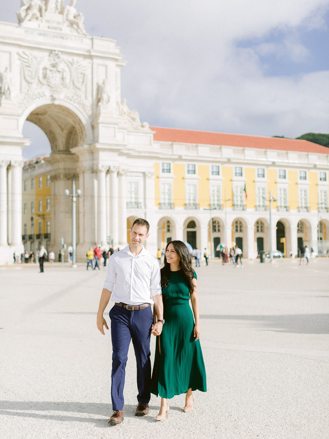 Couple walking hand in hand with Lisbon landmark behind by Portugal Wedding Photographer