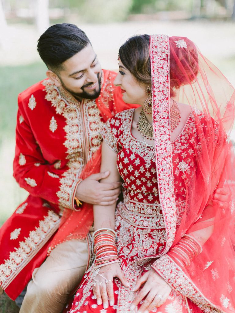 Indian Groom and Bride with traditional red and gold gowns by Portugal Wedding Photographer