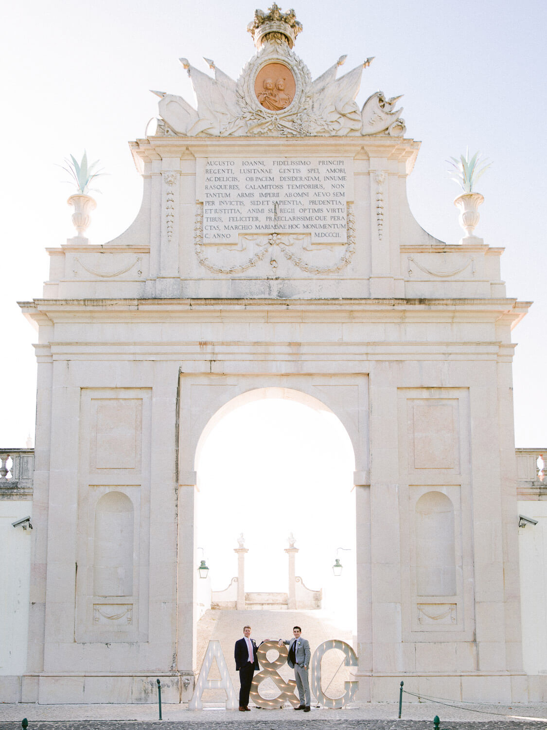 groom and groom posing by Palace de Seteais triumphal arch by Portugal Wedding Photographer