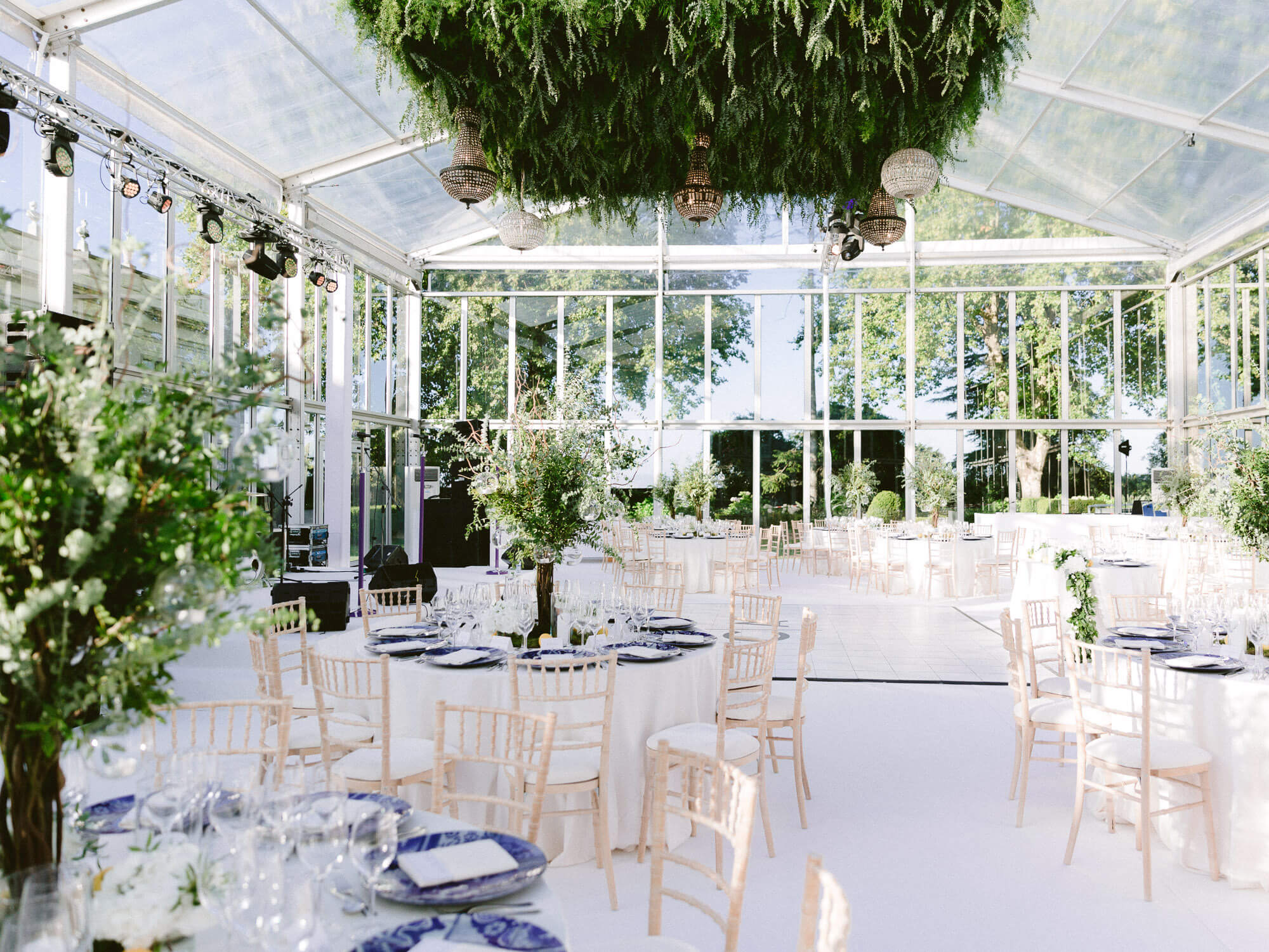 wedding reception dinner in transparent tent and greenery ceiling with crystal chandeliers by Portugal Wedding Photographer
