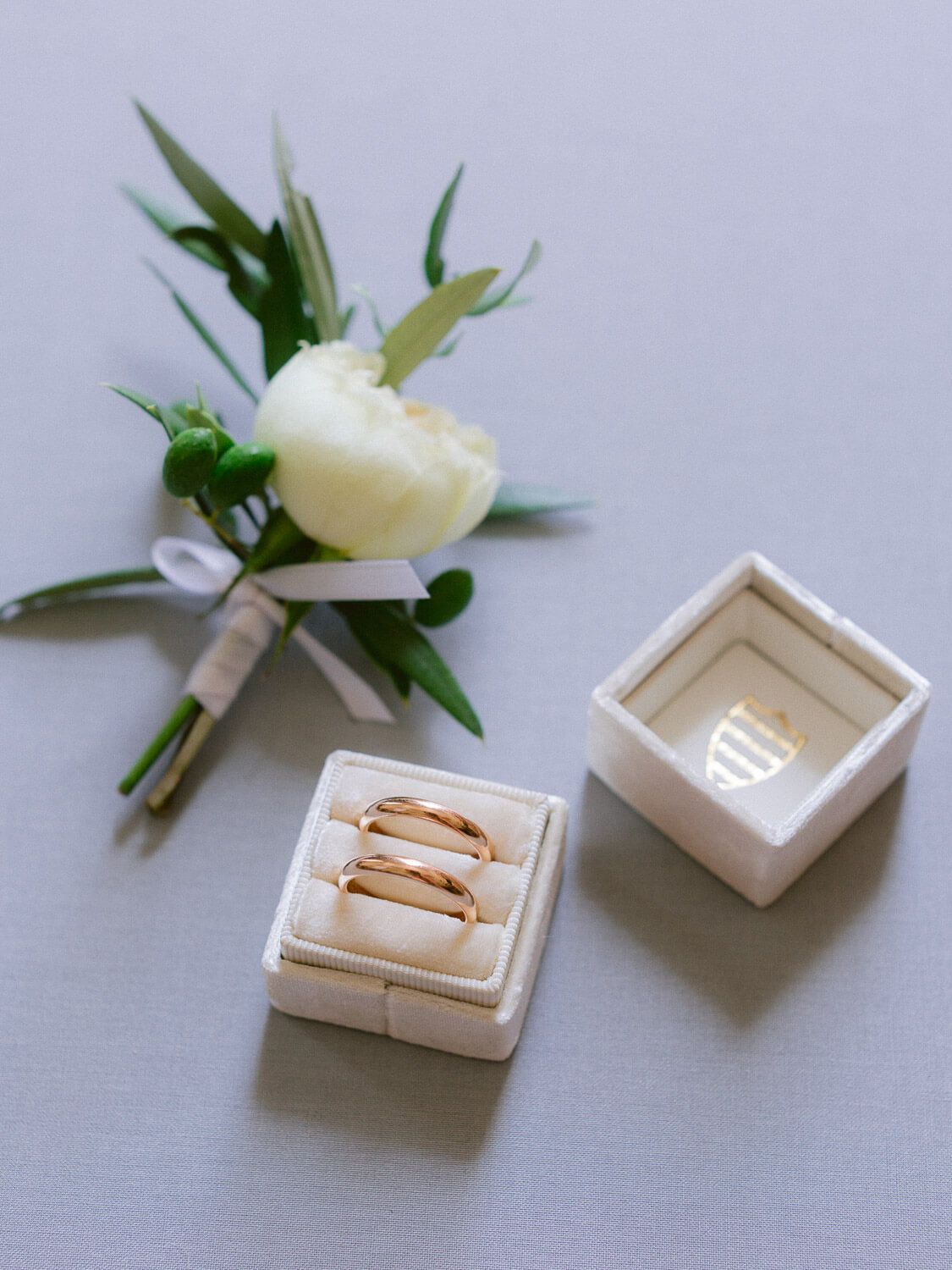 boutonnière and wedding bands on off white velvet ring box by Portugal Wedding Photographer