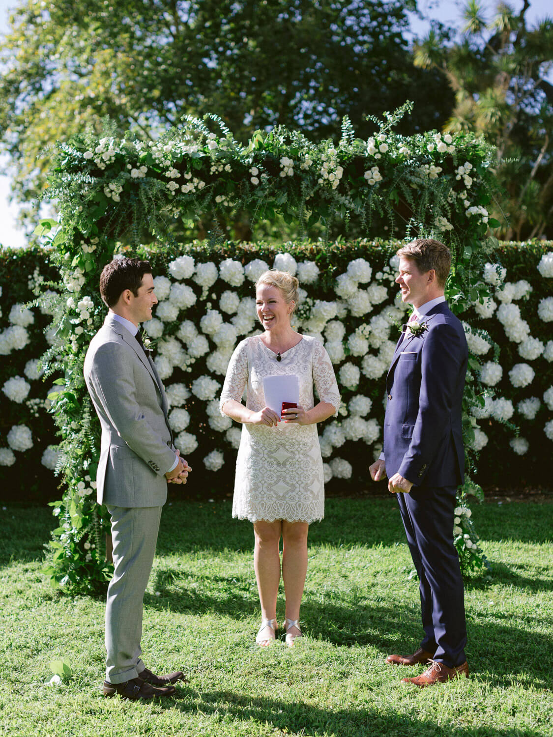 wedding ceremony celebration with a floral arch and white hydrangeas backdrop by Portugal Wedding Photographer