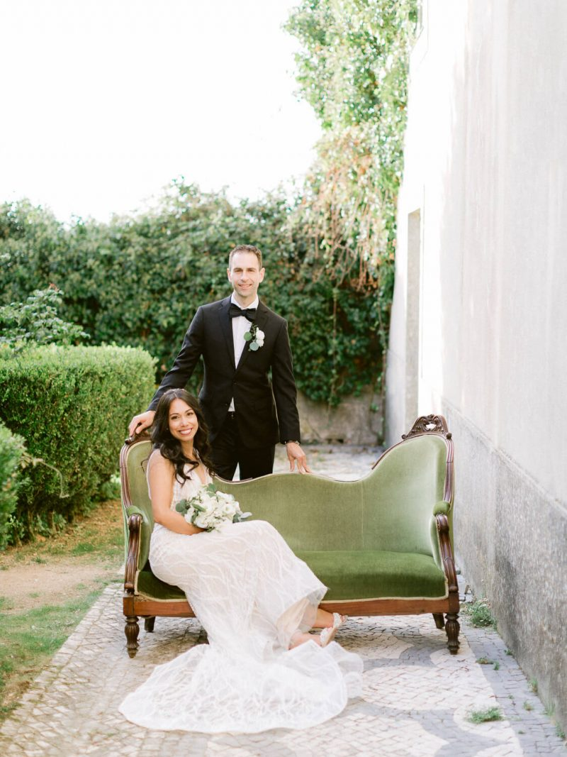 newlyweds posing with vintage green velvet settee by Portugal Wedding Photographer