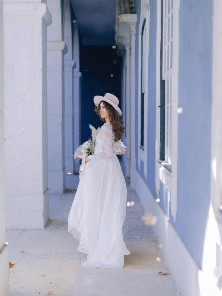 Bride is looking back while walking in the galleries of Palacio Queluz